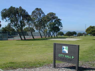 Public tennis court and sign with text &#34City Hall&#34 and arrow pointing in direction of city hal