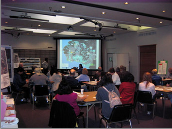 People sitting in a room, looking at information on projector screen